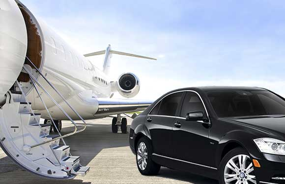 A luxury sedan from Commonwealth Worldwide's General Aviation fleet parked outside of a private jet.