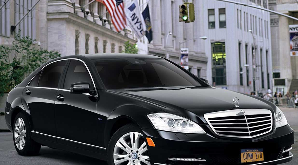 A luxury sedan from Commonwealth Worldwide's fleet, parked in the heart of New York City's financial district.